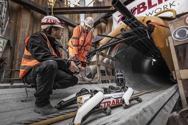 Zwei Züblin-Mitarbeiter bedienen den Roboterhund Spot